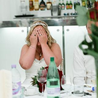 Bride covering face with hands