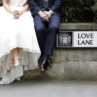 Couple sitting by Love Lane sign